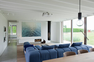 Modern living room with glass wall and blue sofa