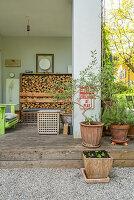 Überdachte Veranda mit Holzlager, im Vordergrund Pflanzentöpfe