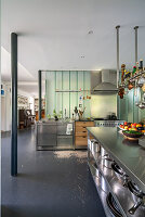 Island counter with stainless steel shelves below in open-plan interior