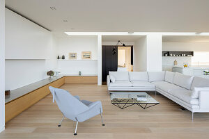Pale sofa set, coffee table, armchair and low, custom sideboard in open-plan interior
