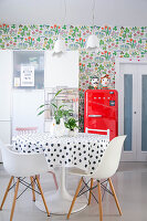 Dining area, red fridge and white kitchen cabinets against floral wallpaper