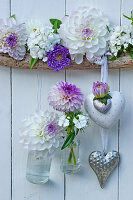 Heart decorations and small suspended bottles holding dahlias, asters and sweet Williams