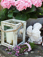 Hydrangea, candle lantern, angel statue and posy of pink forget-me-nots