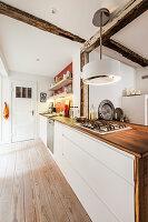 Weiße Einbauküche mit Holzarbeitsplatte