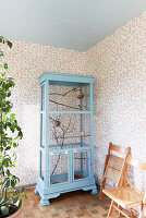 Pale blue aviary made from old cupboard against floral wallpaper