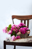 Pink roses in metal vases on chair