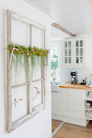 Ornamental window frame with summer garland on wall