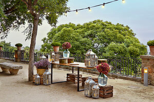 Table, lanterns, hydrangeas in demijohns and wooden crates