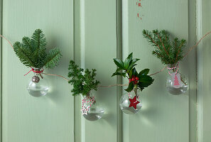 Handmade garland of glass vases holding Christmas arrangements