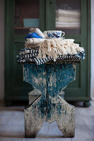 Folded tablecloths and cup on stool