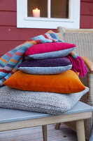 Cushions with covers in autumnal colours and knitted blanket