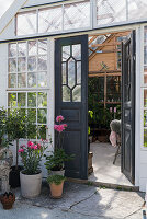 Open double doors leading into idyllic summerhouse made from old windows