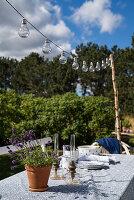 String of light bulbs above rustic garden table
