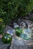 Charming arrangement of glass balls and pebbles in garden