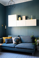 Blue sofa with scatter cushions below white wall-mounted cabinets on blue living room wall