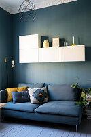 Blaues Polstersofa mit Kissen, darüber weißer Hängeschrank im Wohnzimmer mit blauer Wand