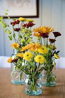 Blumen in Gelbtönen in Glasgefäßen