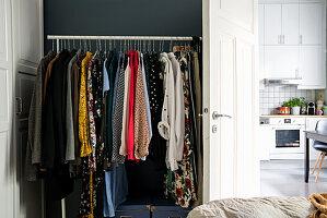 Kleiderständer im Schlafzimmer neben geöffneter Tür, Blick in die Küche