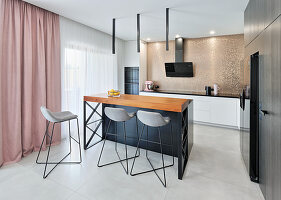 Kitchen counter with bar stools in open-plan kitchen with shimmering gold mosaic tiles