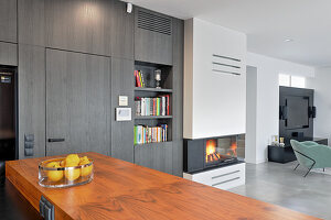 View across kitchen counter with wooden worksurface to bookshelves and fireplace in open-plan interior