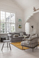Armchair with grey cushions and matching sofa next to window in white-painted log cabin