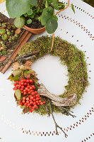 Moss wreath with viburnum berries and twigs on white metal table