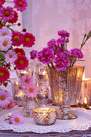 Romantic arrangement of carnations, ox-eye daisies and tealights on table