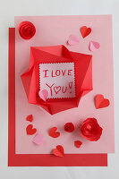 Love note in origami envelope on pink and red paper