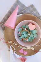 Arrangement of sweets, paper cone and string of lettered beads on plate