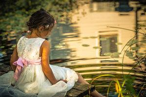 Girl in white summer dress sitting on jetty next to idyllic pond