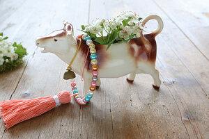 Milchkännchen in Kuh-Form mit Obstblüten auf dem Holztisch
