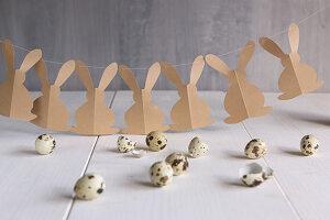 Girlande mit Hasen aus braunem Papier und Wachteleier