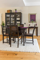 Dark dining set in front of crockery in black display cabinet