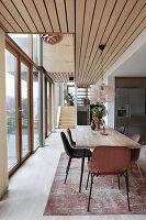 Esstisch mit Stühlen vor Fensterfront in offenem Wohnraum, im Hintergrund Treppenaufgang