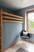 Loft bed and classic chair next to window in pale grey child's bedroom