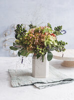 Autumn bouquet with hydrangea flowers, witch grass and tufts of unripe olives