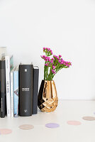 Books and flowers in gold vase