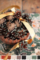 Christmas arrangement of pine cones and gold ribbon in rusty cake tin