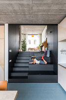 Boy lying on steps with dark wood cladding and steps of different heights leading to living room