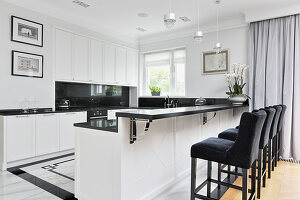 Black upholstered chairs at breakfast bar in luxurious, open-plan kitchen