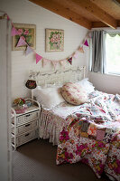 Old bed with colourful, vintage-style bed linen and rattan bedside table below bunting on wall