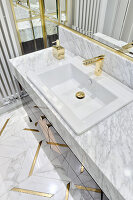 Gold tap and details in luxurious bathroom with marble elements