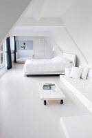 Minimalist, white bedroom below sloping ceiling