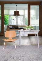 Designer chair and small, old table in front of sliding door leading into dining room