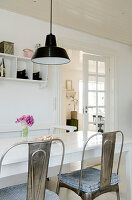 Metal chairs at the dining table with black ceiling light