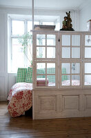 Room dividers made of old windows and a coffered door in a bedroom