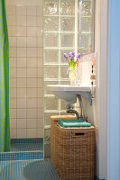 Laundry baskets under a sink in front of the shower with glass block windows