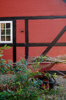 wheelbarrow with green waste on the red half-timbered house in autumn