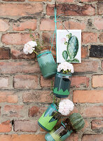 Screw jars covered with paper grass as planters with geraniums and cacti