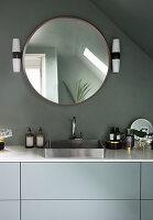 A round mirror above a washbasin